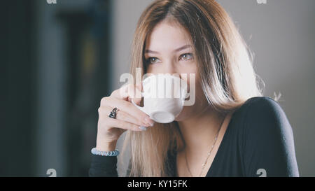 Pretty blonde young woman drinking coffee and smiling in the cafe - Stock Photo