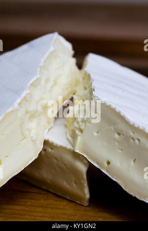 Close up of Camembert cheese. Brie with coarse edge broken into pieces cremy and delicious. - Stock Photo