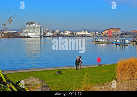 A couple walking  around Cardiff Bay. with St David's Hotel,Pierhead bldg (red), Welsh Assembly Bldg (Senydd) & Millennium Centre(gold) in background.