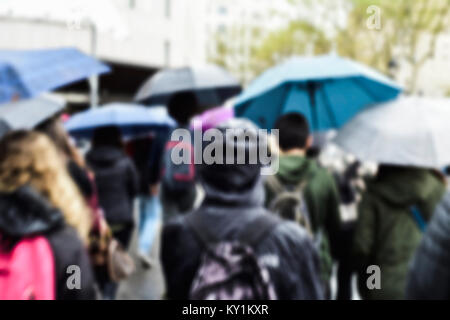 a defocused blur background of people walking under the rain protected by umbrellas in a street of a city - Stock Photo