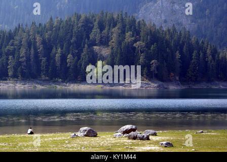 Lonely woman on the Black lake, Durmitor, Montenegro - Stock Photo