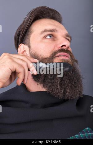 Closeup of hairdresser combing beard of a young handsome man. Studio shot - Stock Photo