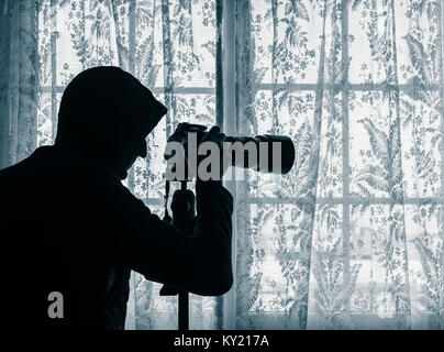 Man wearing hoodie at window looking at LCD screen of camera which has telephoto lens attached. Concept image for - Stock Photo