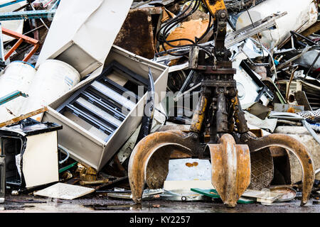 Powerful mechanical grabbing arm is the force that moves old scrap metal and used household appliances in a scrap - Stock Photo