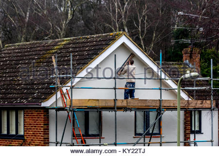 A workman using a long wooden spatula to apply the finishing touches to the white rendering on the gable end of - Stock Photo