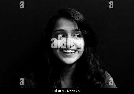 Black and white portrait of a cute, chubby girl looking away, smiling, over black background. - Stock Photo