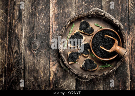 Sandwiches with black caviar on the old tray. On wooden background. - Stock Photo