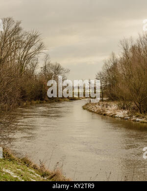 Pastel color outdoor snowy landscpae panoramic photography of a river, a view over fields to the horizon, taken - Stock Photo