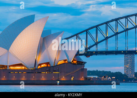 The Sydney Harbour Bridge and Opera House lit up just on dusk viewed from the Royal Botanic Gardens - Stock Photo