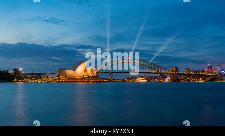 The Sydney Harbour Bridge and Opera House lit up with special lights in preparation for New Year's Eve just on dusk - Stock Photo