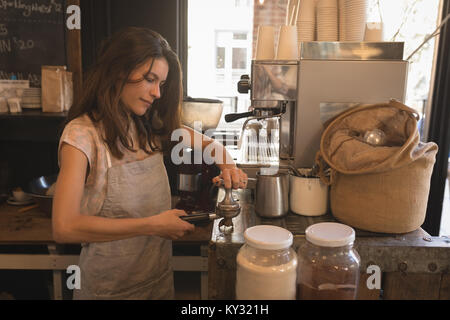 Barista using a tamper to press ground coffee into a portafilter - Stock Photo
