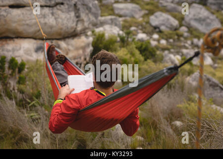 Hiker lying in hammock reading novel - Stock Photo