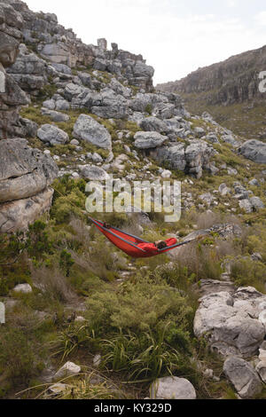 Hiker relaxing in hammock - Stock Photo