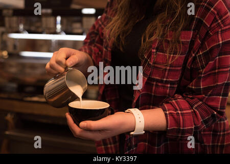 Mid section of female barista preparing coffee at counter - Stock Photo