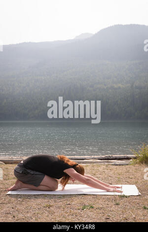 Fit woman doing acrobatic yoga near the sea coast - Stock Photo