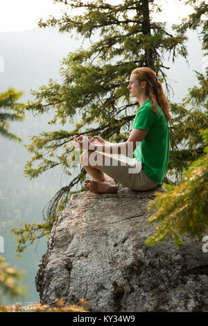 Fit man sitting in meditating posture on the edge of a rock - Stock Photo