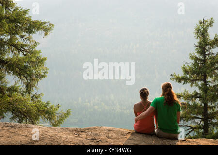 Sporty couple sitting near each other on the edge of a rock - Stock Photo