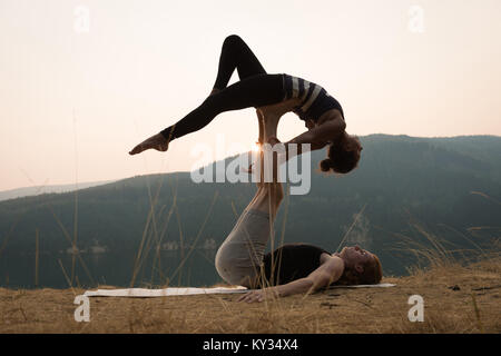 Sporty couple practicing acro yoga in a lush green ground - Stock Photo