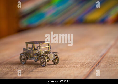 Vintage metal car toy with colorful books on a shelf in the background - Stock Photo