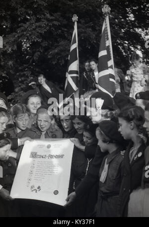 1950, historical picture of a group of excited young girl guides with Union jack flags and holding up a 'message - Stock Photo
