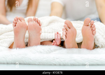 Happy familiy in bed. Mother father and baby feet under blanket. Tree pairs of legs - Stock Photo
