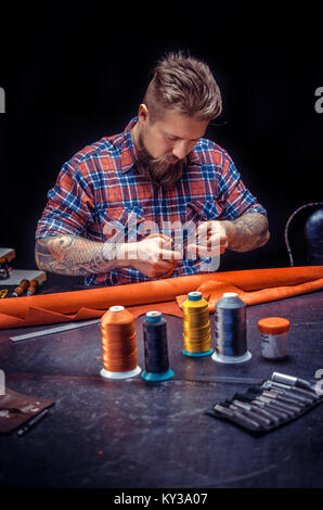 Leather Worker working with leather using crafting tools in the place of work - Stock Photo