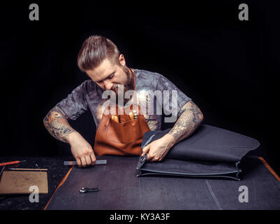Leather Craftsman focusing on his work in his leather studio - Stock Photo