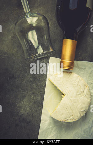 Soft French Camambert Cheese with Cut out Wedge on White Parchment Paper Empty Glass Wine Bottle on Dark Stone Background. - Stock Photo
