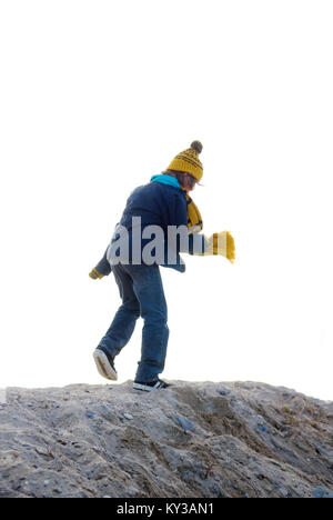 a ten year old boy with wooly bobble hat and scarf runs along the top of a sand dune on a bright and windy day - Stock Photo