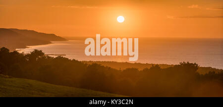 Sunset by the sea with the town of Bastad (Båstad) below. Panoramic view from the Hallandsas at the Bjare peninsula, - Stock Photo