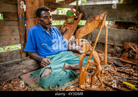Man from the Asmat Tribe carving with a chisel a statue. Asmat man was making a wood carving. June 27, 2012 Jow - Stock Photo
