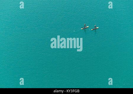 Aerial view of two unidentified stand up paddle boarders on the lake - Stock Photo