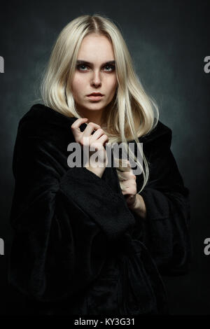 scared girl in black coat on dark background looking at camera - Stock Photo