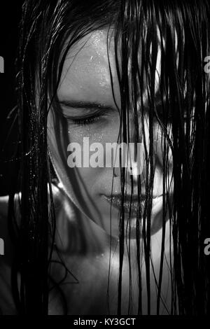 serious sad woman with wet black hair close her eyes in dark, monochrome - Stock Photo