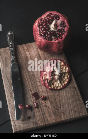 pomegranate and seeds freshly opened on wooden table - Stock Photo