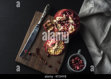 pomegranate and seeds freshly opened on wooden table Stock Photo