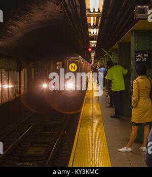 New York, New York State, United States of America.  Train arriving at Lexington Avenue New York City Subway station. - Stock Photo