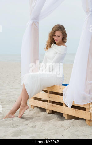 Beautiful woman in white dress is sitting on the beach on the beach couch - Stock Photo