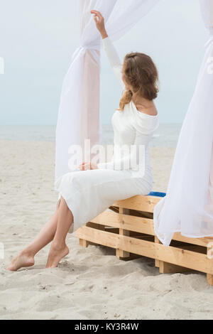 Beautiful woman in white dress is sitting on the beach and is waving her hand - Stock Photo