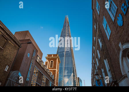 The Shard tower viewed from a street of old brick buildings in London, United Kingdom - July 2017 - Stock Photo