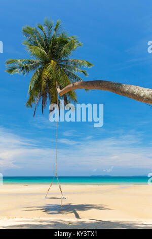 Wooden swing hanging on the beach on tropical island. - Stock Photo
