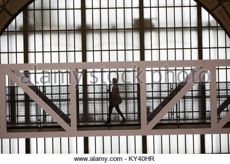 Woman crosses a bridge in The Musée d'Orsay. - Stock Photo