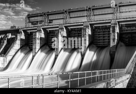SClose up of soft water in long exposure rushing out through gates of a steel and concrete dam in black and white - Stock Photo