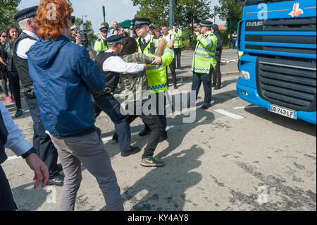 Police move a protester carrying the 'Occupy the Arms Fair' flag from in front of a lorry going to the DSEi Arms - Stock Photo