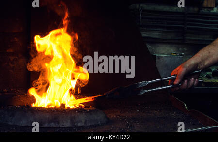 Blacksmith at work, hit with a hammer by a hot metal on the anvil. - Stock Photo