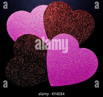 Four different colored, glittery hearts together on a black background - Stock Photo