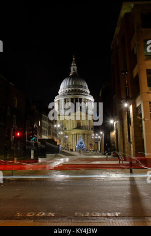 Saint Paul's Cathedral at night looking North from Queen Victoria street, with light trails from passing buses. - Stock Photo