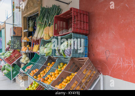 Fruit market with various fruits and vegetables displayed outdoors, in crates, with a colorful red wall background, - Stock Photo