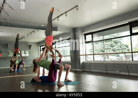 Group of fit people practicing acroyoga - Stock Photo