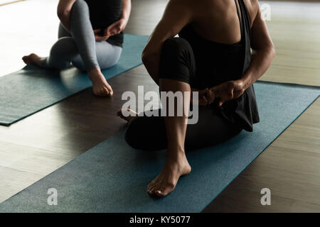 People practicing yoga on exercise mat - Stock Photo